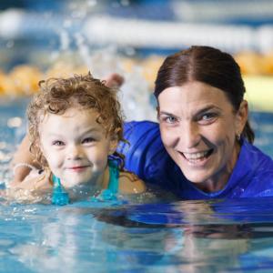 child swimming with teacher